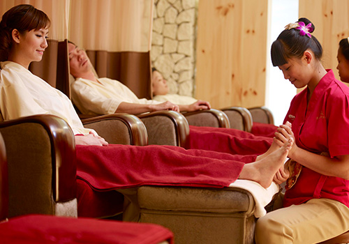 Woman enjoying foot massage at Kenko Wellness