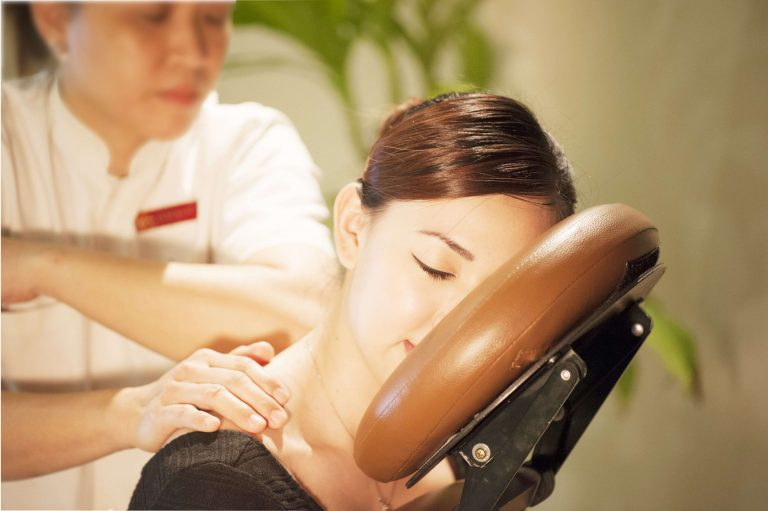 Woman receiving shoulder massage on seated chair at Kenko Wellness